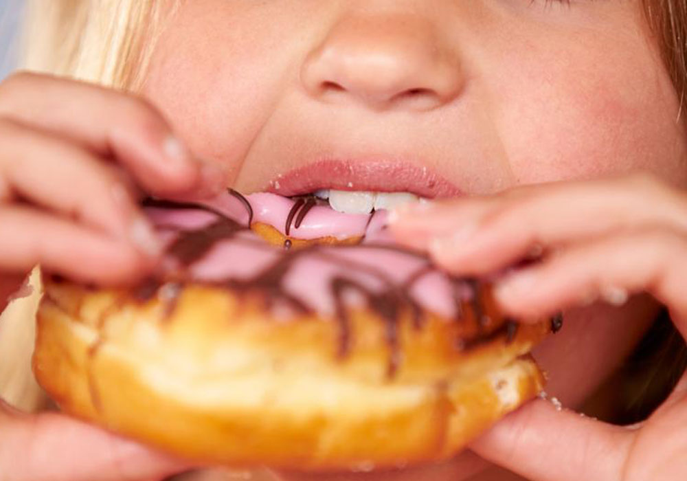 Girl eating a Doughnut - Baby Root Canal Treatment Aurora & Denver